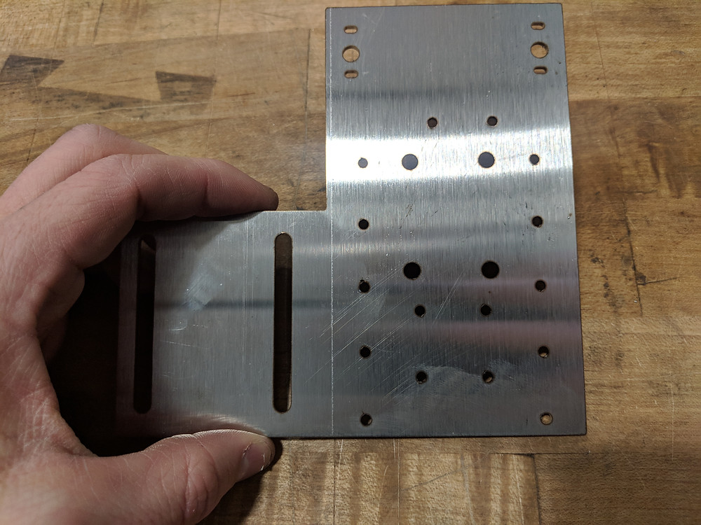 Deck scratching and bottom burr on a laser-cut stainless steel part immediately after a laser-cutting operation.