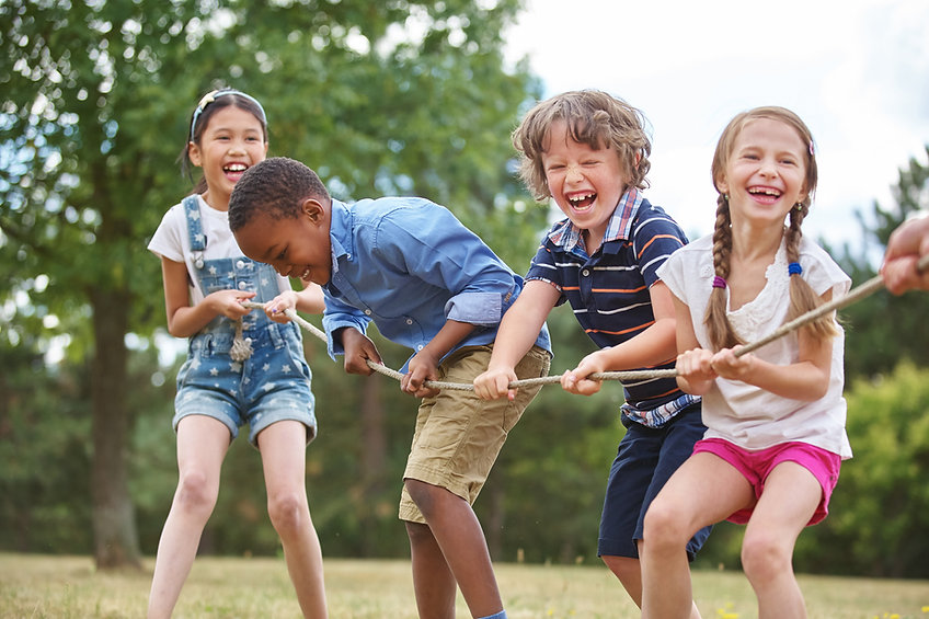 Children playing tug of war at the park.