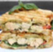 A chicken, cheese, pesto, basil, tomato,