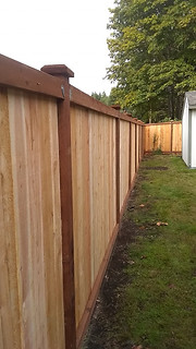 Inset Straightboard Style Cedar Fence with pressure treated rails and bottom face plate