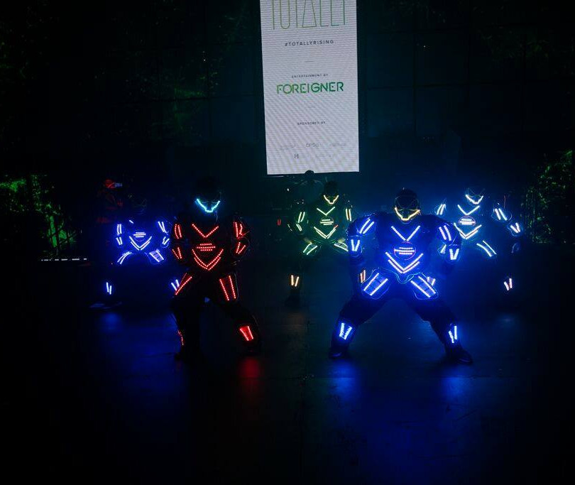 Breakdancers in glowing suits at corporate event