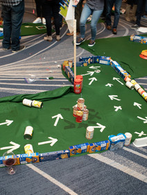 Mini golf course built out of canned goods for team building