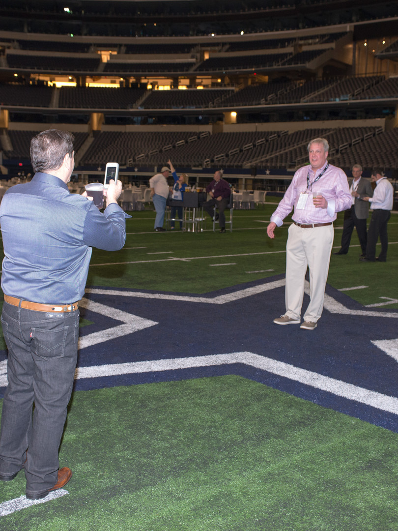 VIP guests standing on Dallas Cowboys football field
