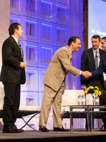 Shaking hands on stage at corporate conference