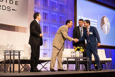 Key Relationships. Men shaking hands on General Session stage.