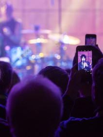 Audience capturing Joan Jett on their phones at customer appreciation party