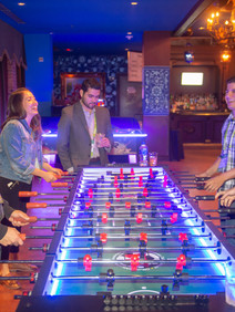 People laughing and playing foosball