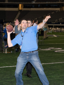 Man throwing football on Dallas Stadium football field at private event