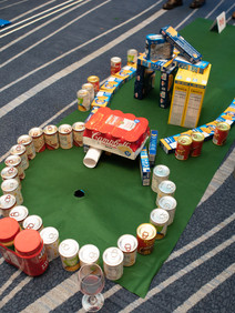 Mini golf course built out of canned goods for donation