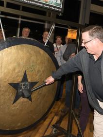 Man hitting gong at customer apprecation event