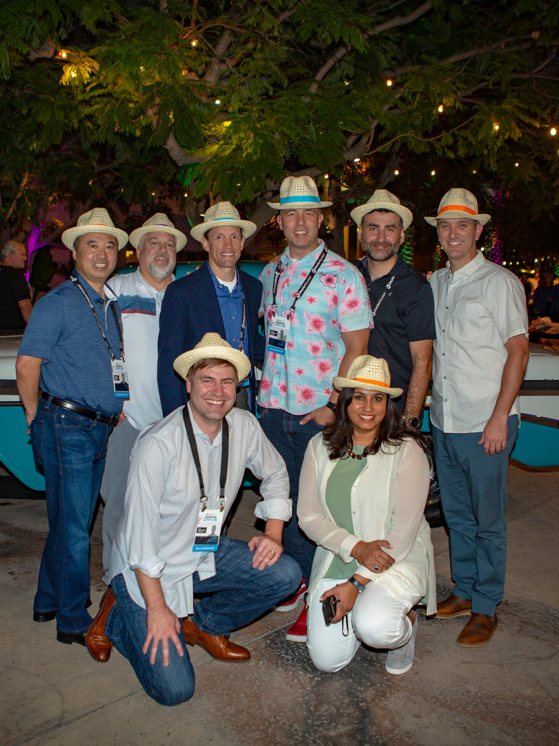 Attendees at evening event posing with fedora hats in front of vintage car