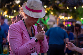 Female customer lighting cigar at Havana Nights themed evening event