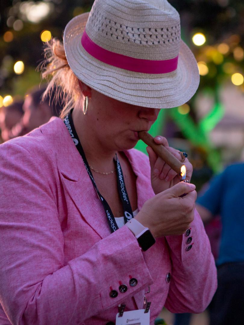 Woman lighting a cigar at Havana themed party