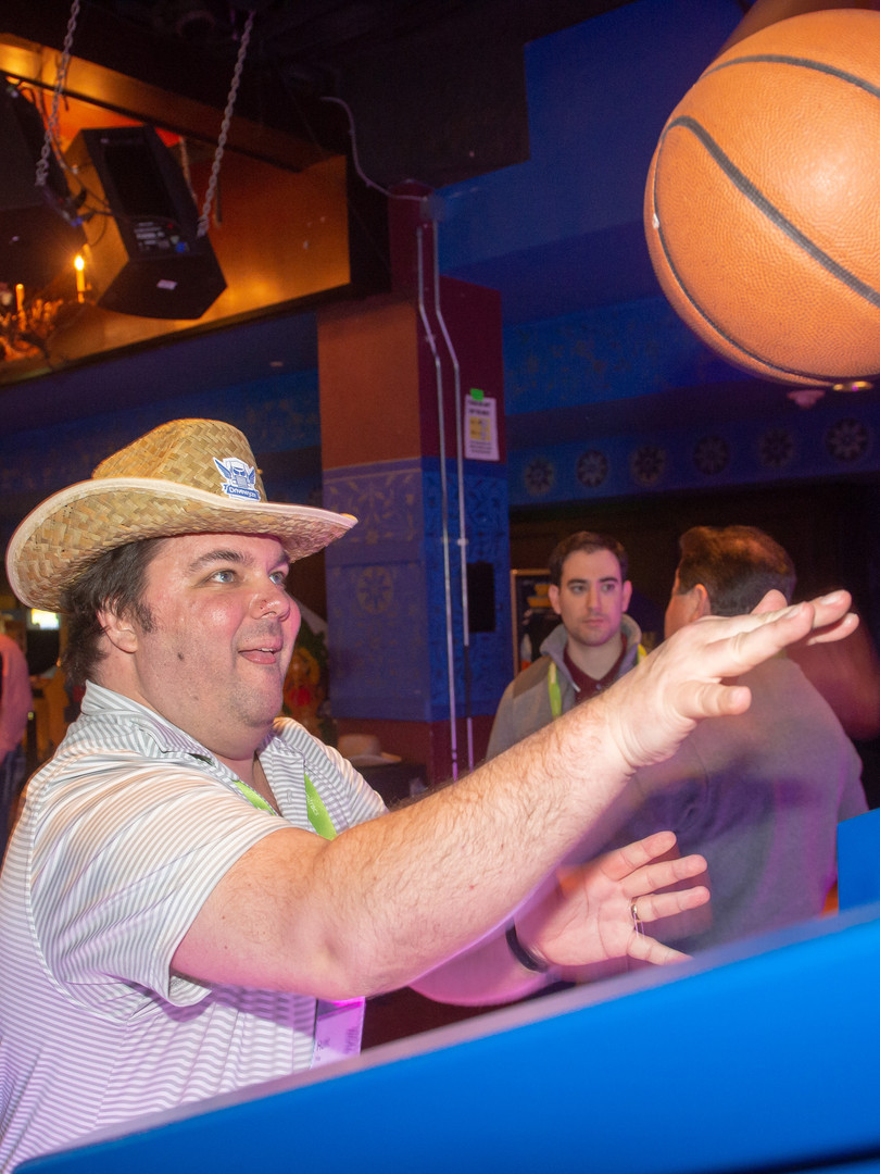Man playing arcade basketball game with cowboy hat on