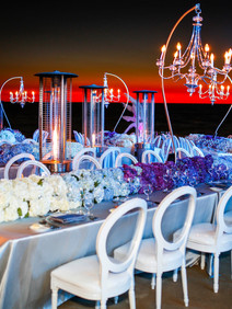 Decorated beach dinner setting with chandeliers