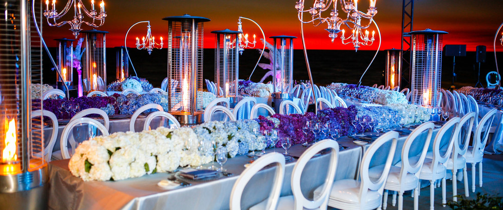 Evening event decor on the beach with tables, white chairs, and chandeliers
