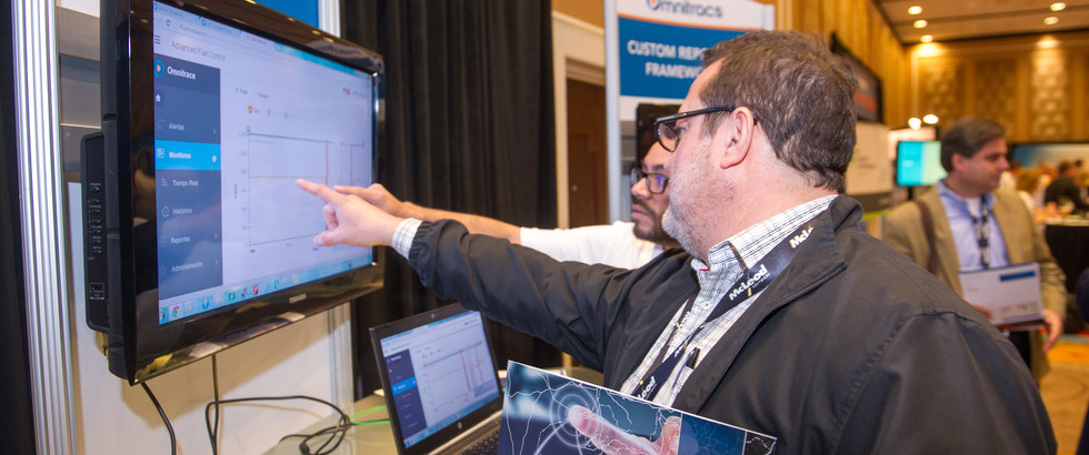 Attendees analyzing data in conference exhibit booth