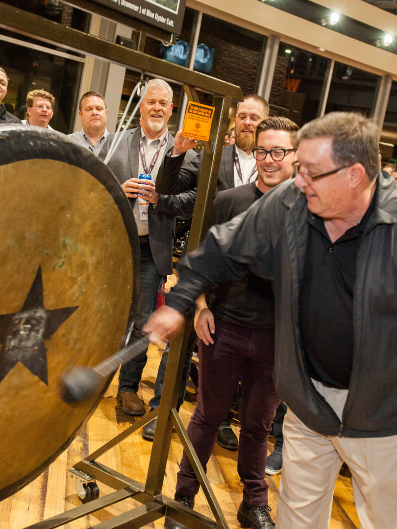 Man banging gong to announce winner at corporate giveaway