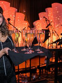 Flapper girl serving champagne flutes at 20's event