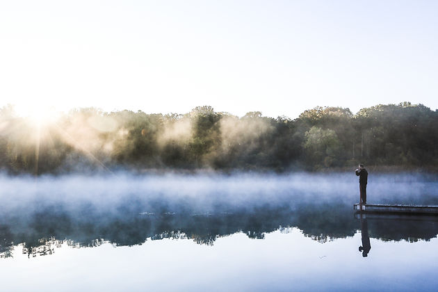 Man on a dock at sunrise