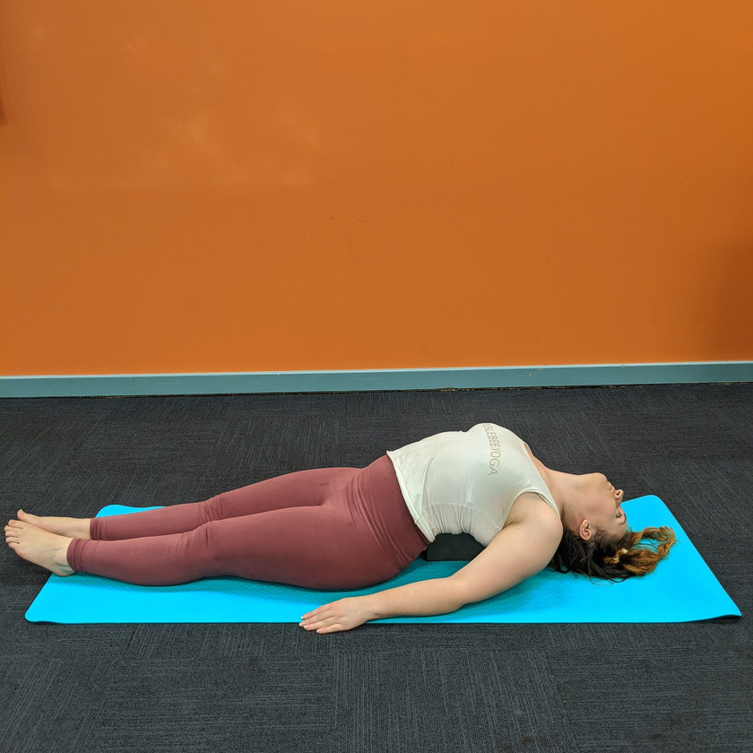 Leah doing fish pose with a block under her upper back