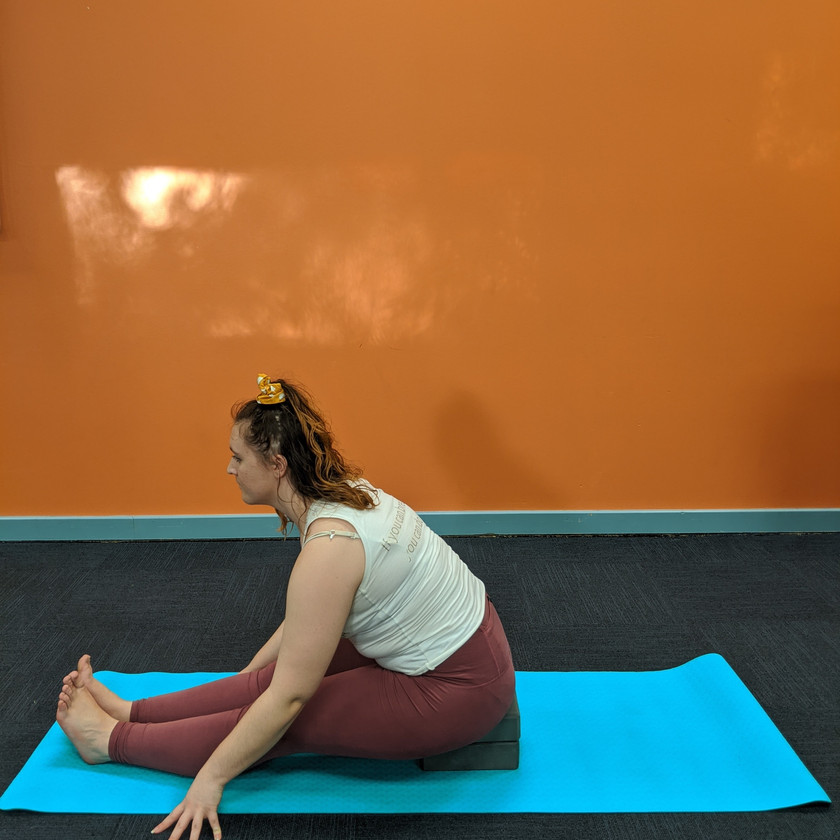 Leah doing a seated forwards fold sitting on two blocks
