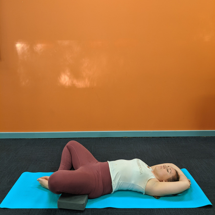 Leah doing reclined butterfly pose with blocks resting under her knees