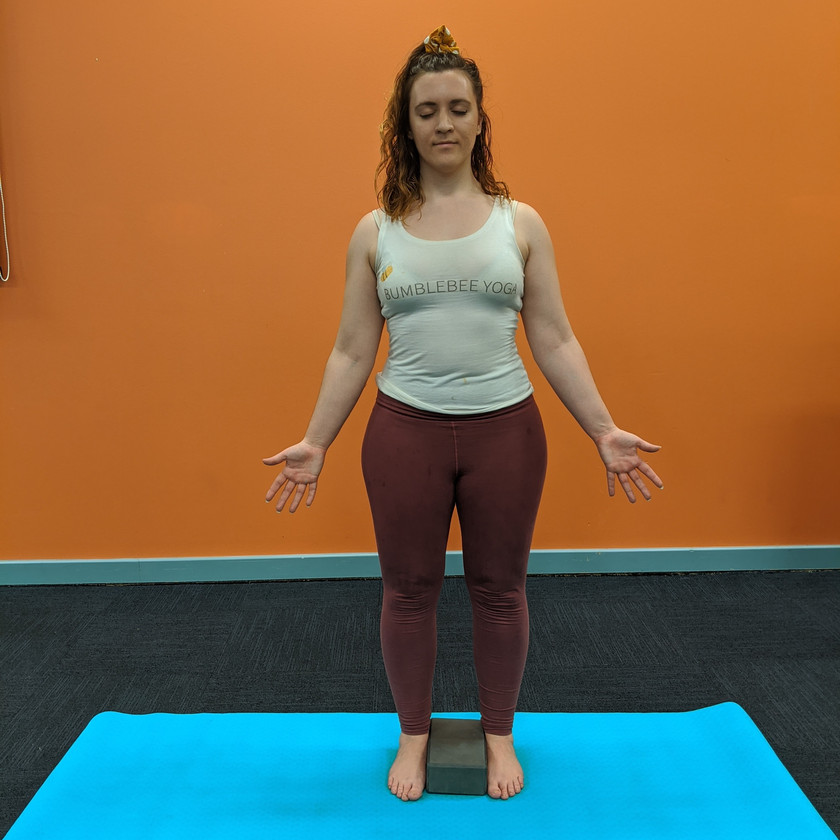 Leah standing with a block between her feet