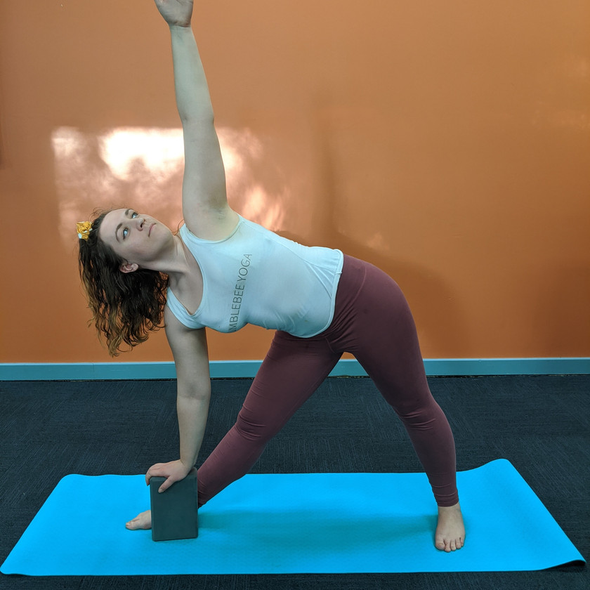 Leah doing a triangle pose with bottom hand on block