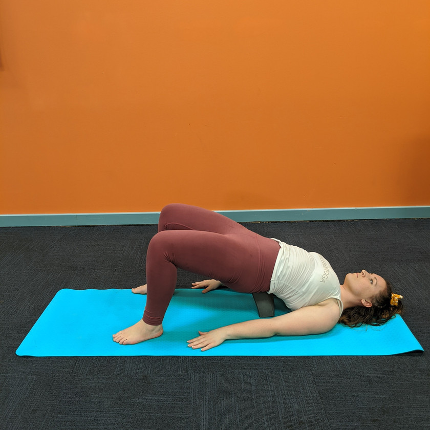 Leah doing bridge pose with a block under her back