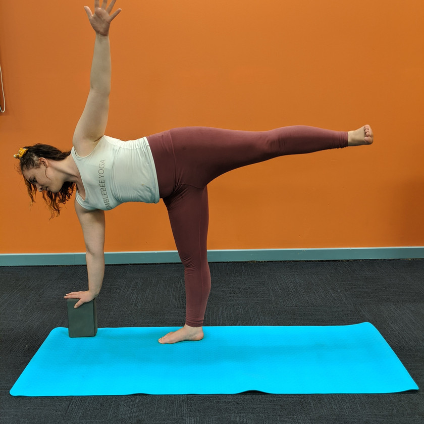 Leah doing floating half moon pose with her bottom hand on a block