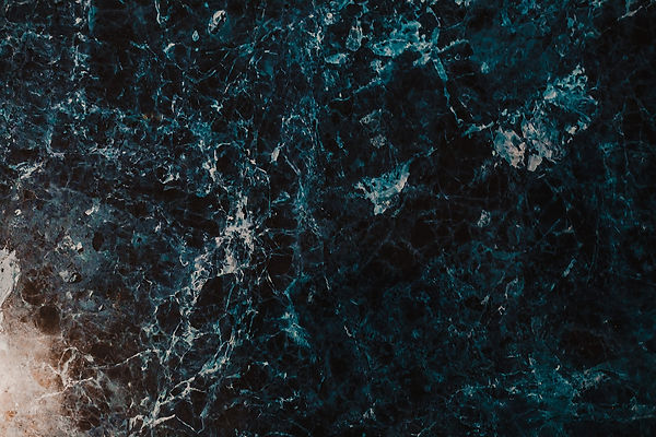dark blue-grey marble with streaks of white that looks like a bird's eye view of the ocean