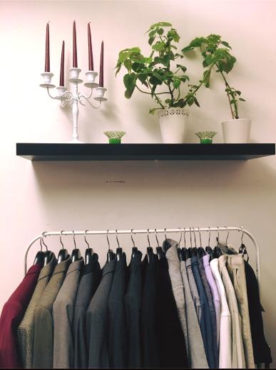 Bild på kläder i ett klädställ med en hylla med gröna växter ovanför.