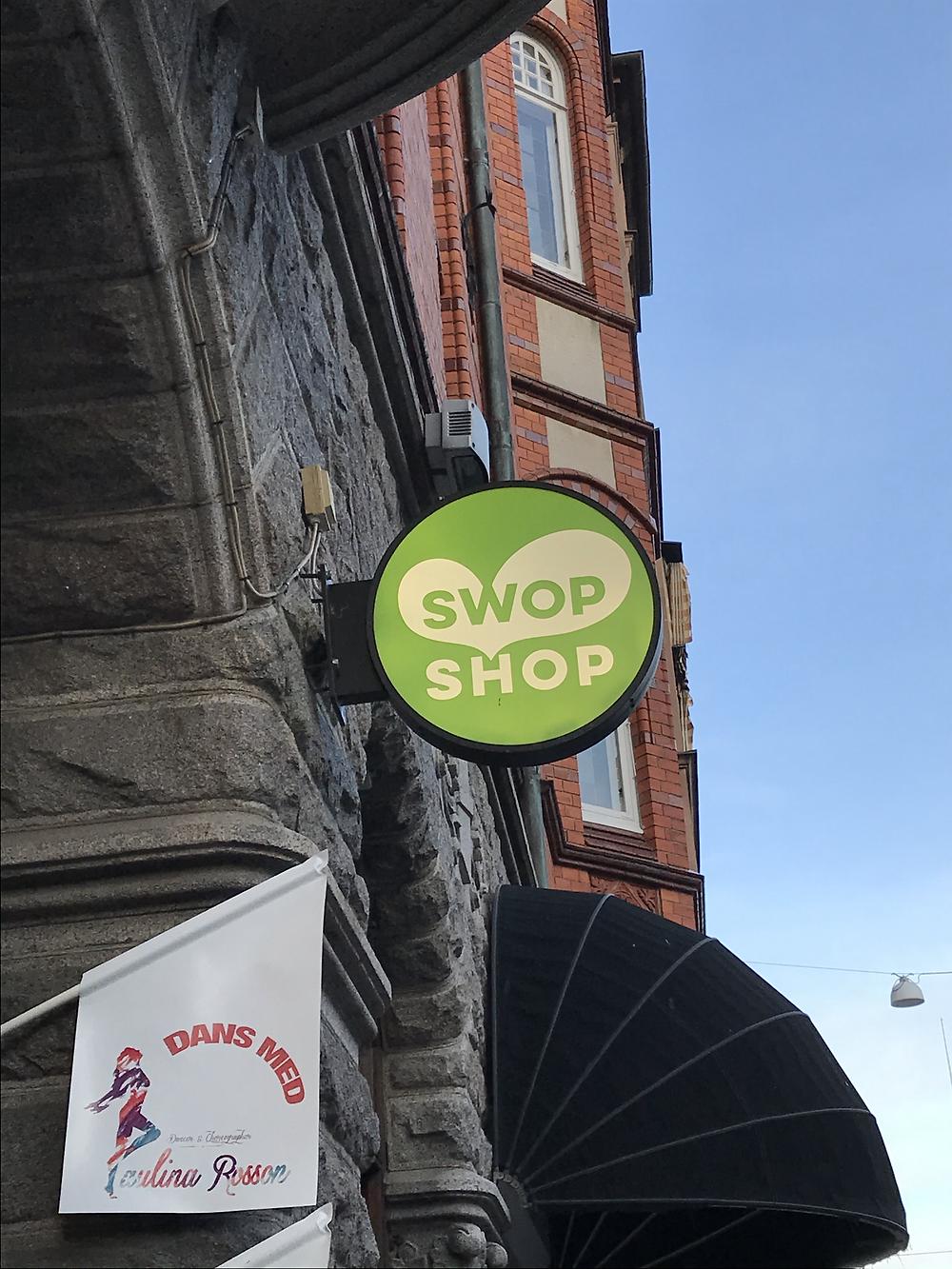 Bild på swop shops butiksskylt som är rund och grön med vit text.