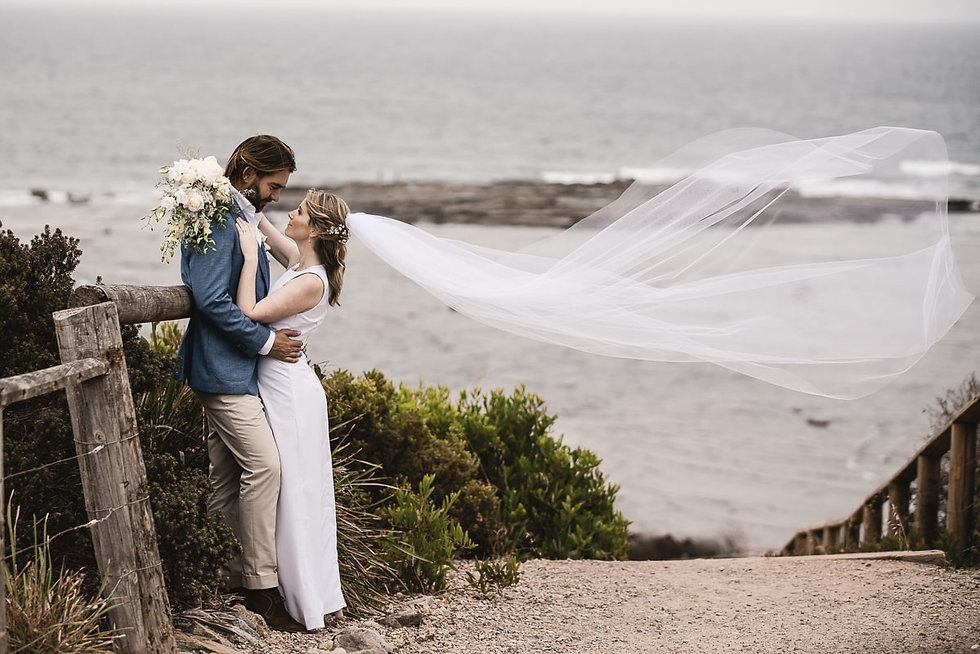 Long Reef Wedding - Bride and Groom embracing with ocean view in the background