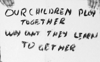 """sign reading, """"Our children play together why can't they learn together"""""""