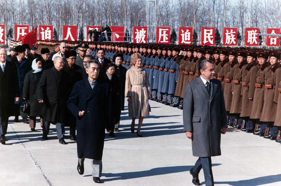 President Richard Nixon inspects Chinese troops upon his departure from Beijing, China. Prime Minister Zhou Enlai walks to Nixon's right.