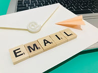 """the word """"email"""" spelled out in scrabble tiles on an envelope with small orange paper plane"""