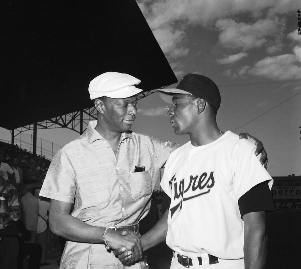 """2/3/1957-Havana, Cuba-Singer Nat """"King"""" Cole (L), congratulates Orestes """"Minnie"""" Minoso, after the latter was voted the """"Arthur Gardner Trophy"""" as the best all-around Cuban ball-player of 1956 in ceremonies at the Grand Stadium."""