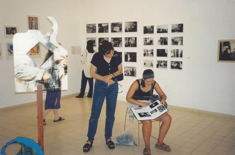 מרחב של מרחקים, אסנת קרסננסקי, עומדת, ליד הספר של מיקי קרצמן, מאי 1999