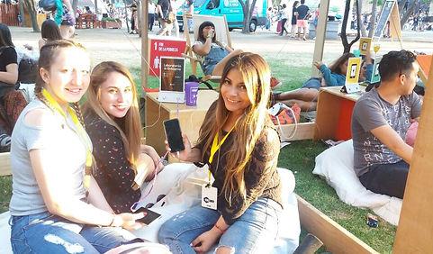 3 jovenes cargando el celular en un evento al aire libre