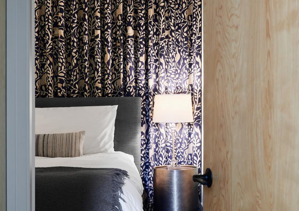 master suite features hardwood floors and custom Robert Allen Pantheon ripple-fold blackout curtain