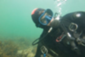 A diver getting used to using his drysuit for buoyancy by lifting the exhaust.