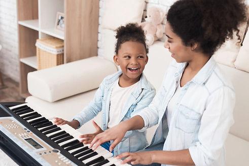 mama-ensena-nina-tocar-piano_85574-1065.