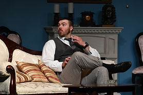 Detective Colquhoun sits on the couch, listening. Scene from The Hollow