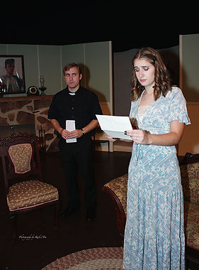Virginia Washington reads a letter. The Vicar Dampier looks on. Scene from The Canterville Ghost.
