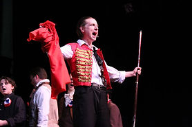 Enjolras holds flag and rallies the students. Scene from Les Miserables.