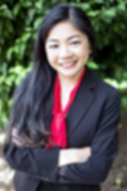 Bonnie Fong wearing a black jacket and red blouse, smiling with her arms crossed