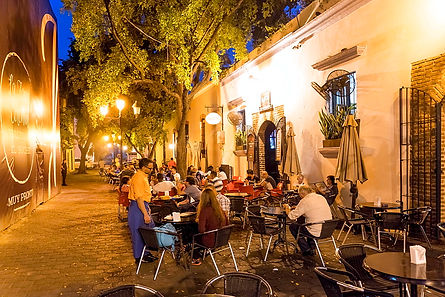 An outdoor dining area where many people are sitting at tables