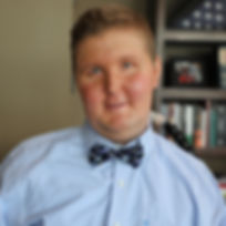 Conrad Reyonoldson wearing a bowtie in front of a book shelf